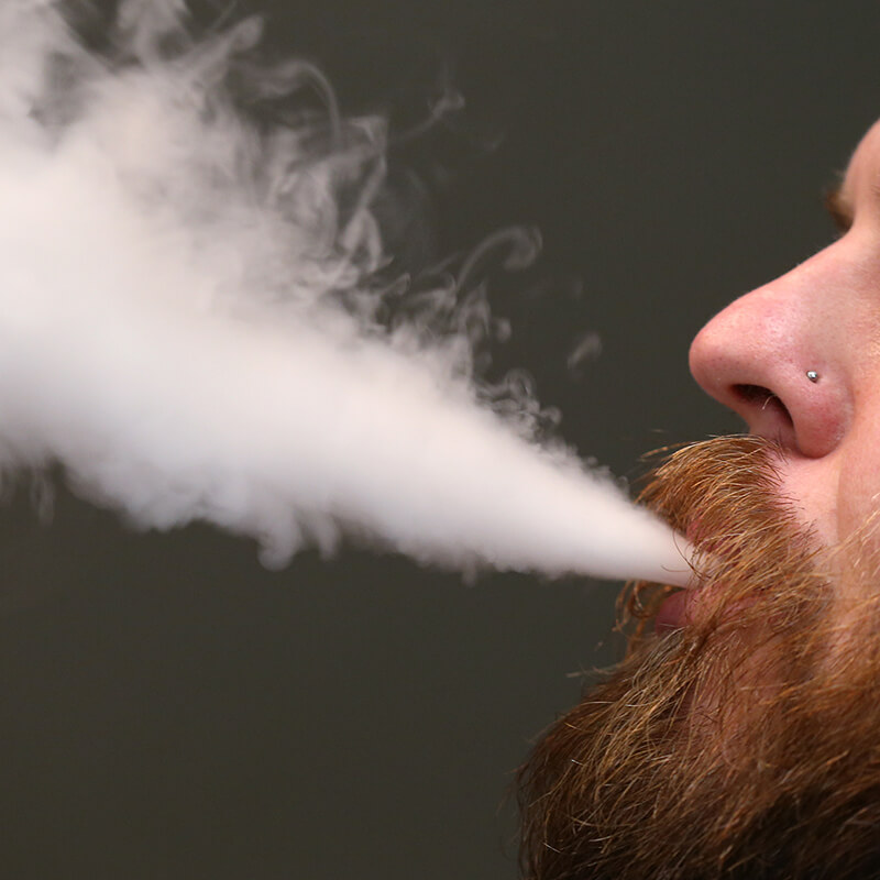 A man with a red beard and mustache, only his mouth and nose showing, exhales e-cigarette smoke in front of a dark gray wall